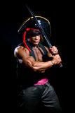 Muscular man in a pirate hat and sword on a black background Royalty Free Stock Image