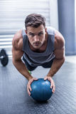 Muscular man on a plank position with a ball. Portrait of a Muscular man on a plank position with a ball Royalty Free Stock Photography
