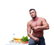 Muscular man pointing at healthy food Royalty Free Stock Photography
