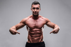 Muscular man pointing at his abs Stock Image