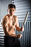 Muscular man posing with a bat Stock Image