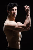 Muscular man posing in dark studio Royalty Free Stock Images
