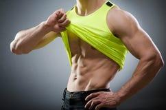 Muscular man posing in dark studio Stock Photo