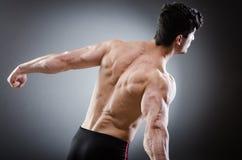 Muscular man posing in dark studio Stock Images