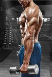 Muscular man posing in gym, showing triceps. Strong male naked torso abs, working out, focus on the hand Royalty Free Stock Image