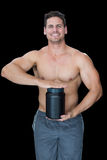 Muscular man posing with nutritional supplement Stock Image
