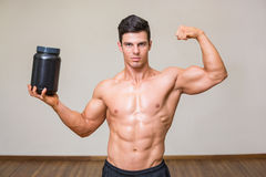 Muscular man posing with nutritional supplement in gym Stock Photography