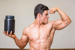 Muscular man posing with nutritional supplement in gym Stock Photo