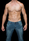 Muscular man posing shirtless in blue jeans Stock Photography