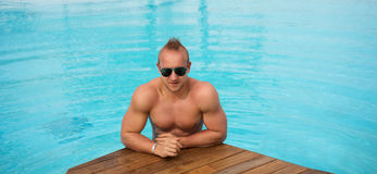 Muscular man posing in the swimming pool Royalty Free Stock Images