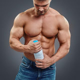 Muscular man with protein drink. Closeup of muscular man torso holding a white bottle with protein drink over grey background. Bodybuilder with milk royalty free stock photography