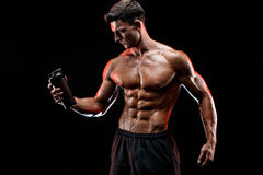 Muscular man with protein drink. In shaker over dark background royalty free stock photo
