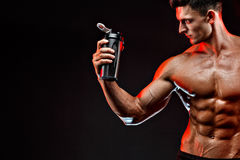 Muscular man with protein drink. In shaker over dark background stock images