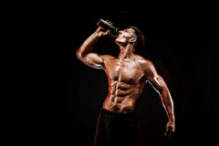 Muscular man with protein drink. In shaker over dark background royalty free stock images