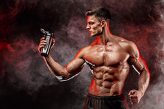 Muscular man with protein drink in shaker. Over dark smoke background stock images
