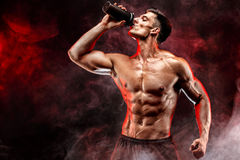 Muscular man with protein drink in shaker. Over dark smoke background royalty free stock images