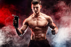Muscular man with protein drink in shaker. Over dark smoke background royalty free stock image