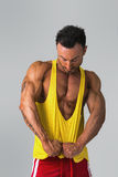 Muscular man pulling down tanktop on torso Stock Photos