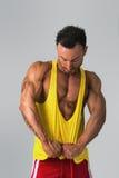 Muscular man pulling down tanktop on torso Stock Photos