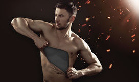 Muscular man pulling his chest skin away Stock Images