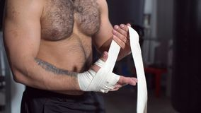 Muscular man putting on punching wraps in fitness studio. Muscular man putting on punching wraps in fitness studio Royalty Free Stock Photo