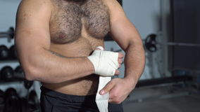 Muscular man putting on punching wraps in fitness studio stock footage