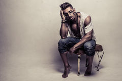 Muscular Man in Ragged Clothes Sitting on a Chair Royalty Free Stock Photo