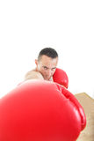 Muscular man with red  gloves hiting to camera. Muscular determined man with red  boxing gloves hiting to camera Stock Photos