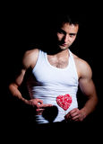 Muscular man with red lollipop Royalty Free Stock Photography
