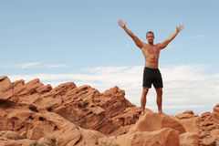 Muscular man on red rocks Royalty Free Stock Photo
