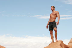 Muscular man on red rocks Stock Photos