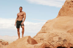 Muscular man on red rocks Royalty Free Stock Photography