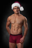 Muscular man in red santa cap on dark background Royalty Free Stock Photos