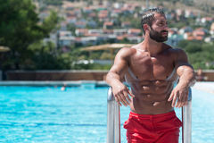 Muscular Man Resting In Swimming Pool Royalty Free Stock Photo