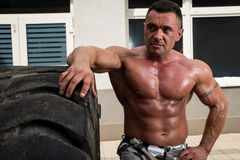 Muscular Man Resting After Tire Flip Royalty Free Stock Photos