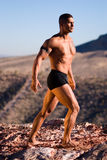 Muscular man on rock. Royalty Free Stock Images