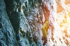 Rock climbing. man rock climber climbing the challenging route on the rocky wall. Muscular man rock climber in bright yellow pants climbing the challenging route royalty free stock image