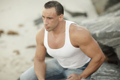 Muscular man on the rocks Stock Photo