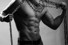 Muscular man with rope. One handsome sexual strong young man with muscular body in blue jeans holding rope with hands hanging on neck and shoulders standing Stock Images