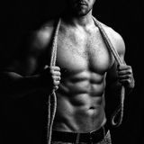 Muscular man with rope. One handsome sexual strong young man with muscular body in blue jeans holding rope with hands hanging on neck and shoulders standing Royalty Free Stock Photography