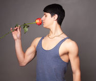 Muscular man with a rose in hands Royalty Free Stock Photography