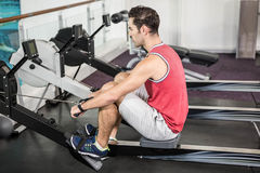 Muscular man on rowing machine Royalty Free Stock Photography