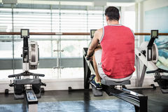 Muscular man on rowing machine Stock Images