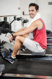 Muscular man on rowing machine smiling at the camera Stock Photography