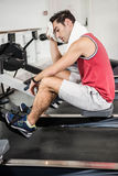 Muscular man on rowing machine wiping sweat with towel Stock Images