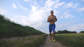 Muscular man running at country road. Young athletic guy jogging at rural trail over the field. Male sportsman training Stock Photos