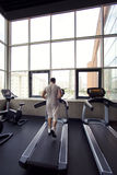 Muscular man running on a treadmill in a fitness club Royalty Free Stock Photos
