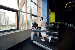 Muscular man running on a treadmill in a fitness club Stock Images