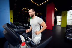 Muscular man running on a treadmill in a fitness club Royalty Free Stock Photo