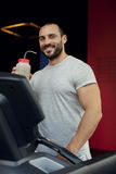 Muscular man running on a treadmill in a fitness club Royalty Free Stock Image